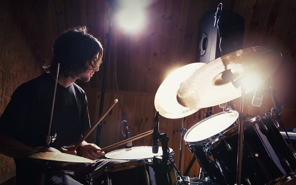 Drummer playing miked drums